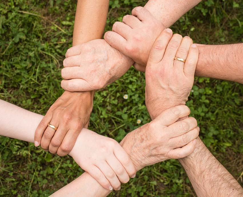 A group of interlocked hands forming a star