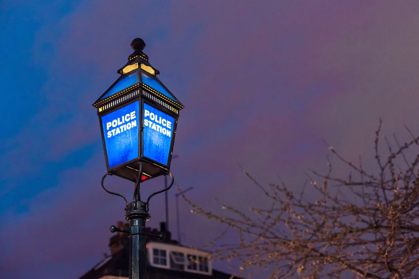 "A illuminated, blue ""Police Station"" outdoor lamp post"
