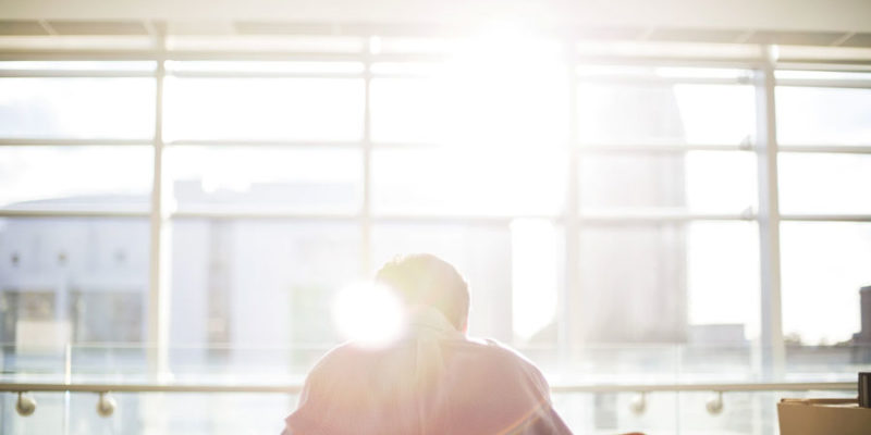 Sun shines on a man sitting at office table