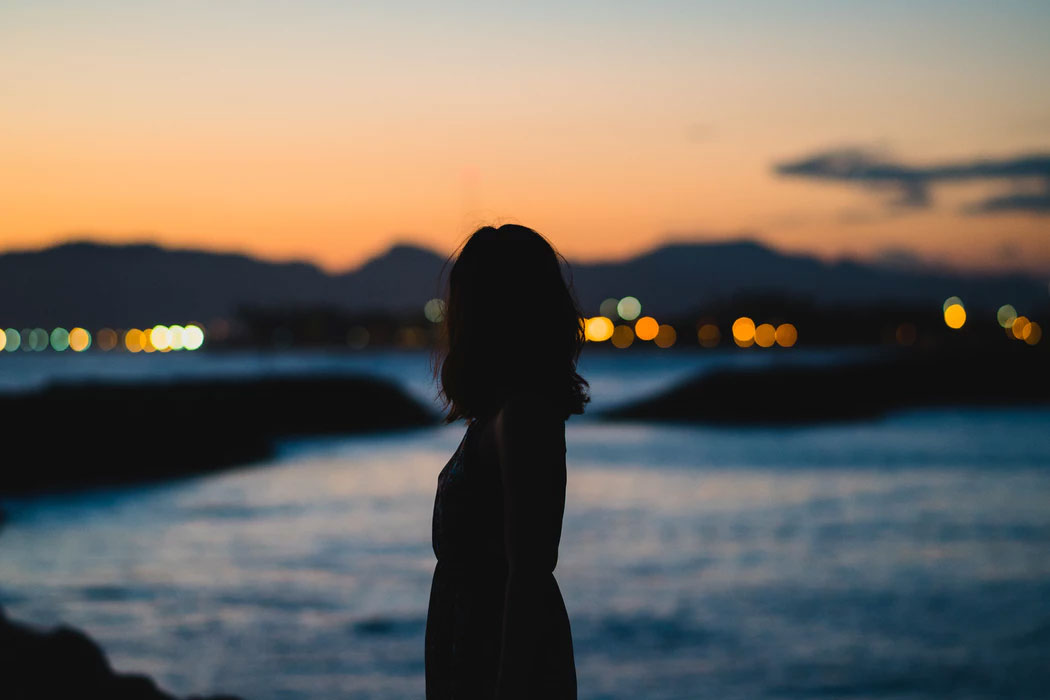 A woman in silhouette standing on the shore in a city at twilight